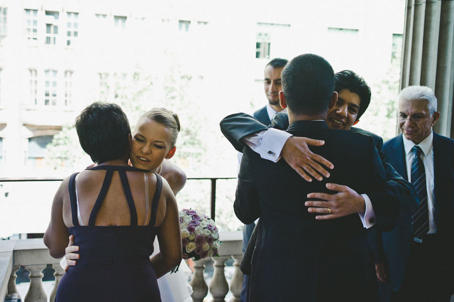 Bride and groom hugging friends together at Melbourne city hall