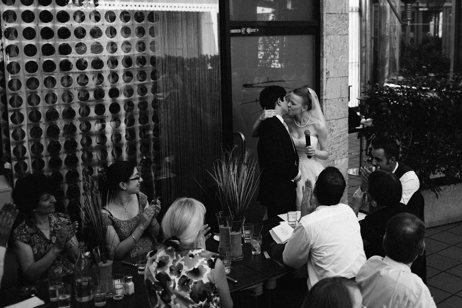 Bride and groom kissing after speech at Bar Italia, Carlton
