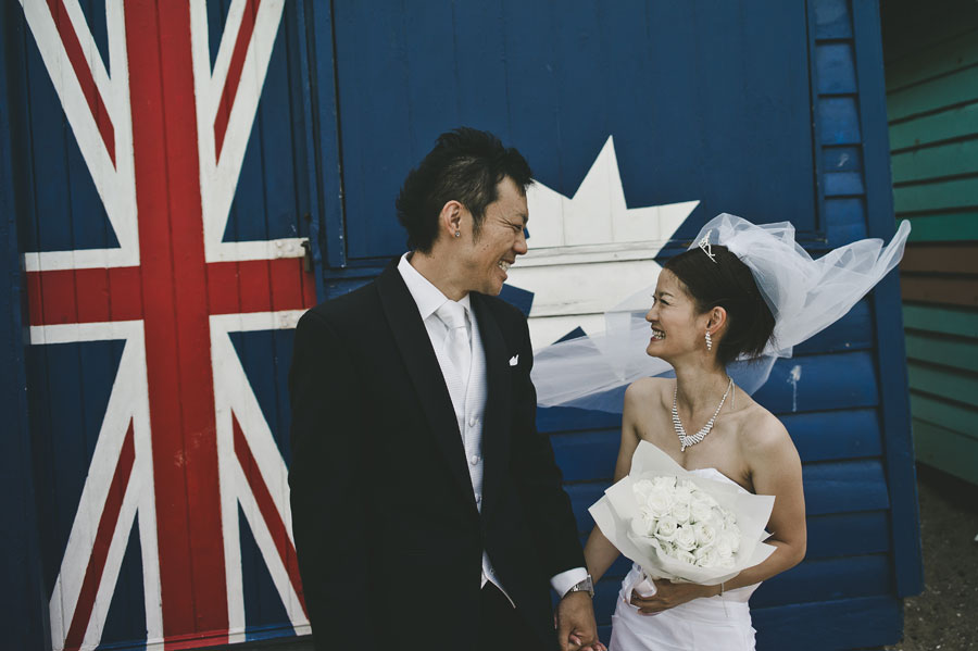Wedding couple smiling in front of Australian cottage