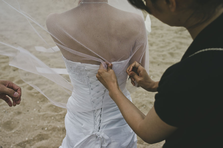 Bride's dress getting adjusted at Brighton beach
