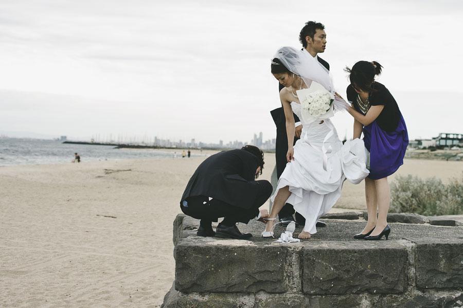 Bride adjusting shoes at Brighton beach