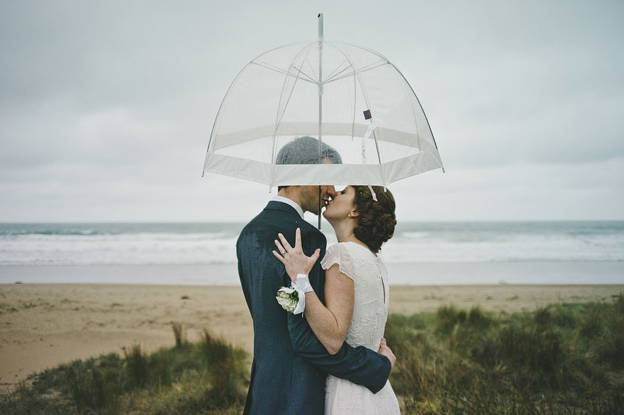 Wedding couple under the umbrella next to Lorne beach