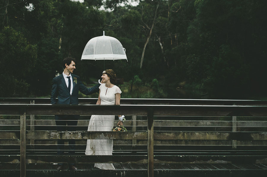 Groom giving bride the shelter on bridge - Lorne, Melbourne