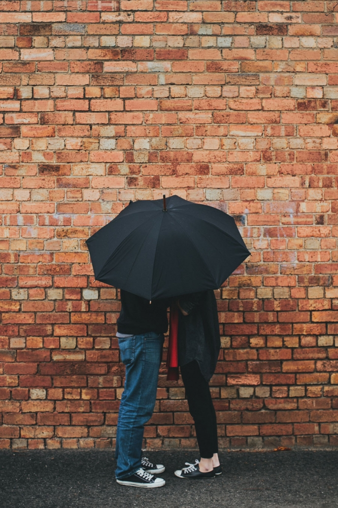 Couple hiding under umbrella engagement