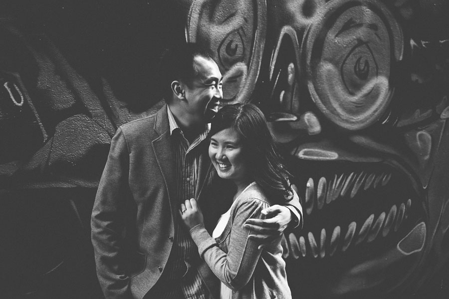 Couple embracing in front of Melbourne graffiti wall