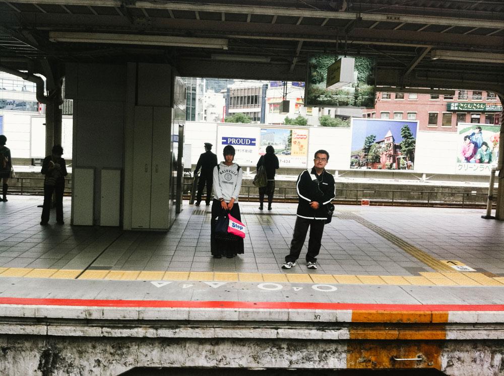 Couple waiting for train in Kobe Japan