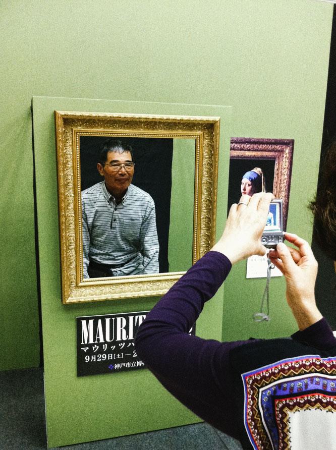 Old man posing like girl with pearl earrings in Kobe.