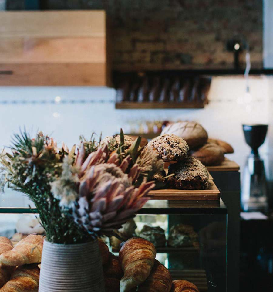 Counter with flower and bread in Northcote Breadshop