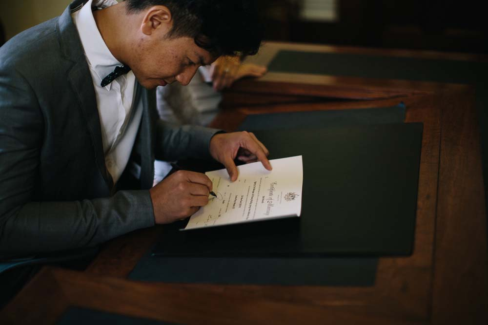 Paul signing the marriage certificate