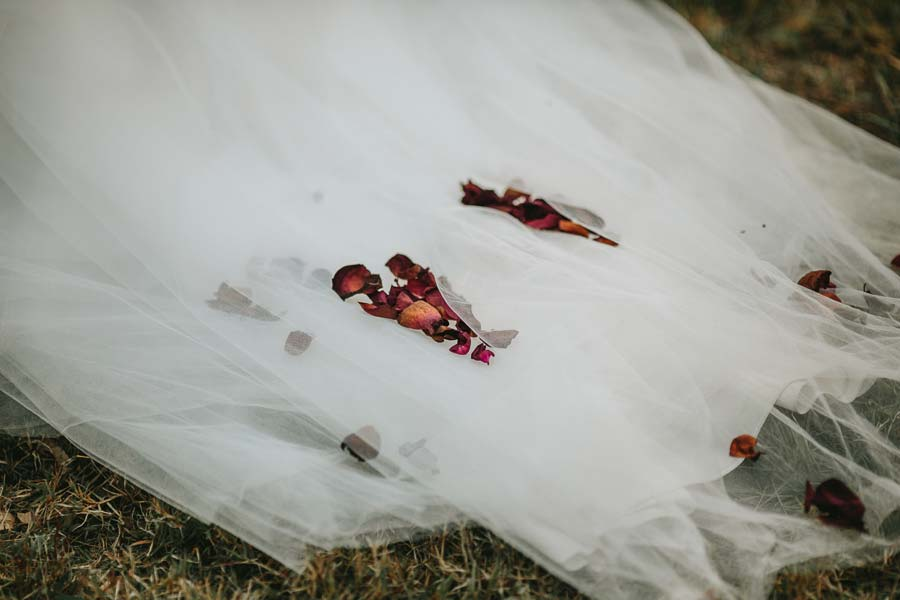 Rose petals on the white wedding dress