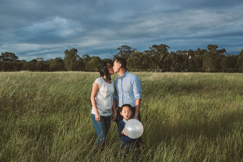 Couple kissing with son and white balloon Melbourne.