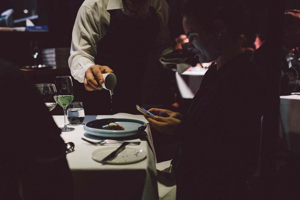 Waiter pouring sauce to Marron dish