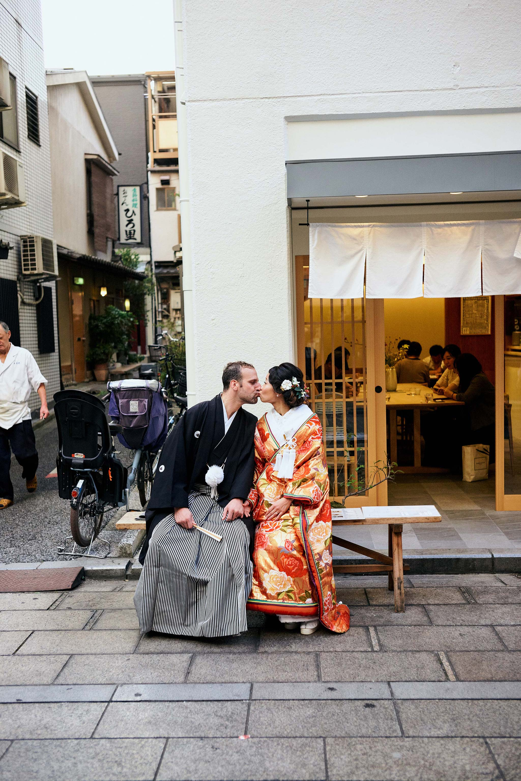 tokyo asakusa shrine traditional wedding couple kissing sitting in front of shop front