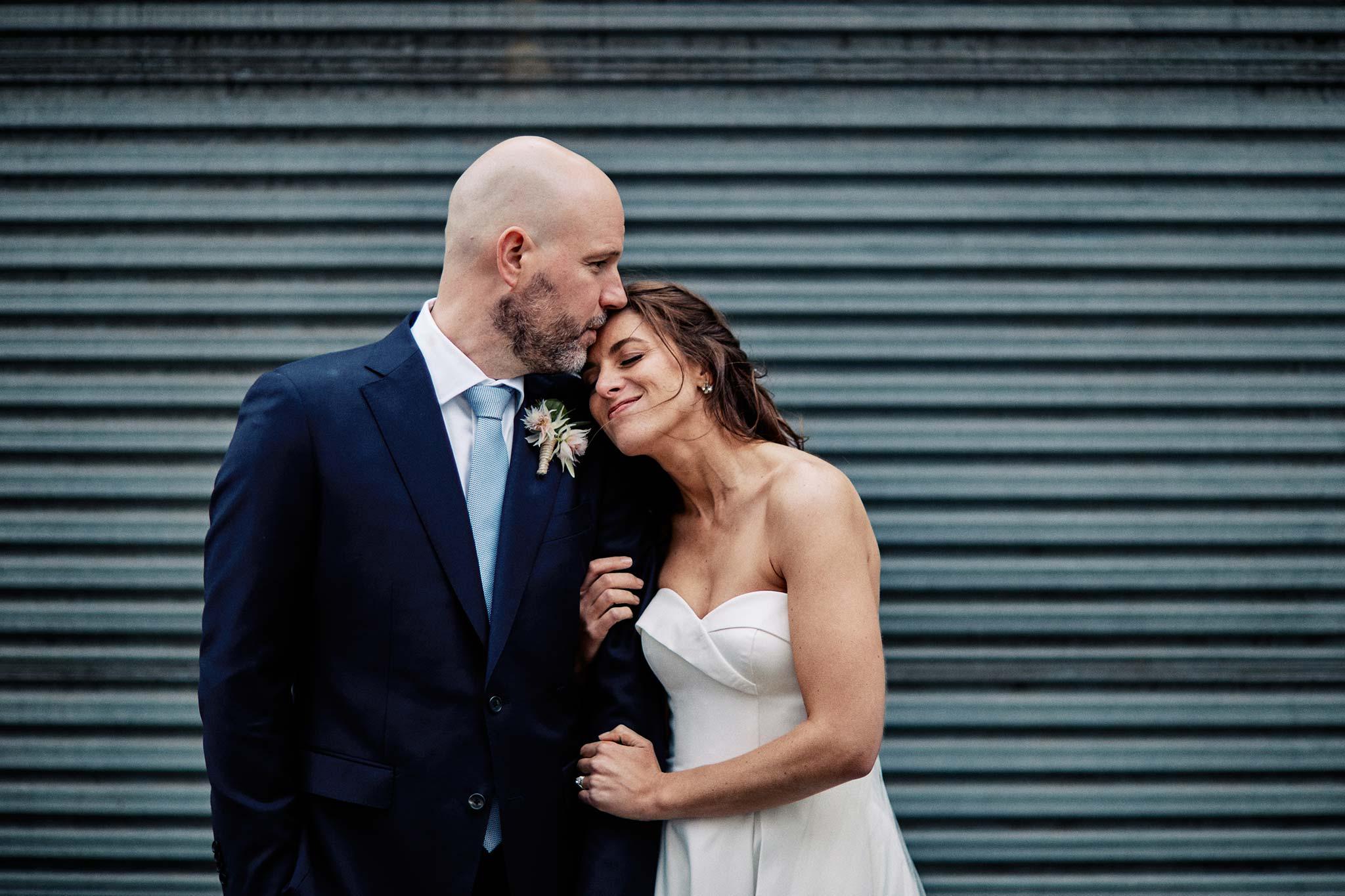East Melbourne Wedding Photographer Bride Groom embrace rustic backdrop