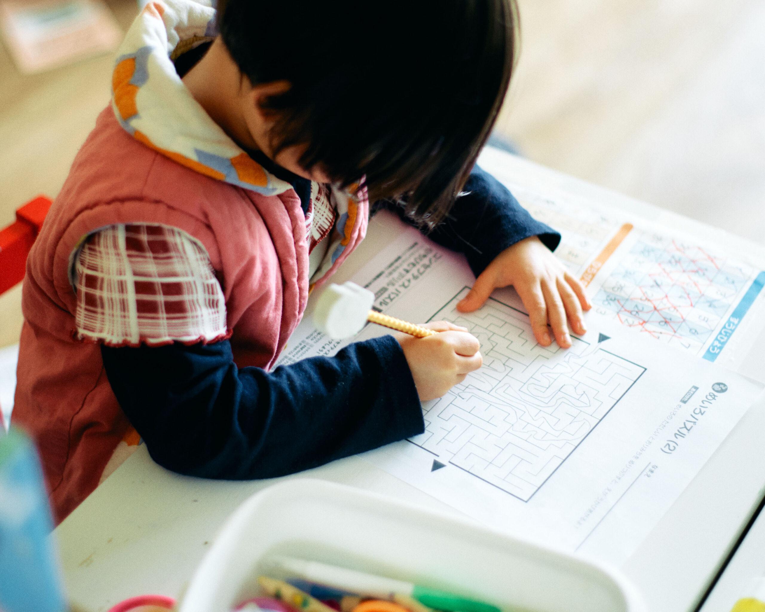kid-solving-maze-puzzle-desk